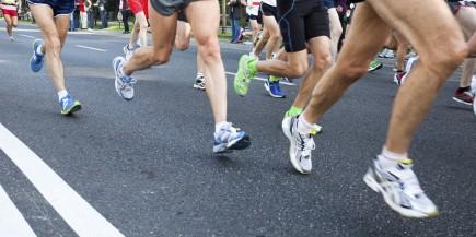 People running in city marathon on street